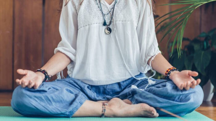 Young woman meditate while practicing Yoga. Sitting in lotus position, relaxing and enjoying incense stick after yoga class.