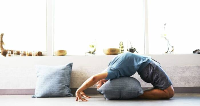 A man doing a modified version of a wheel pose on a pillow