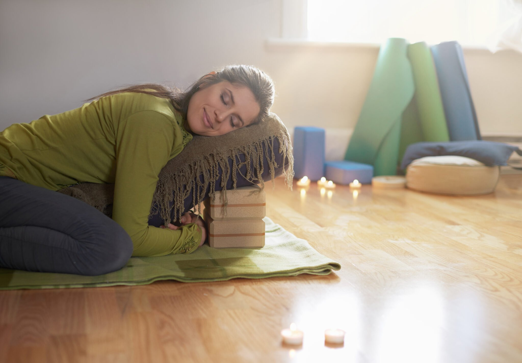 Serene lady relaxing and meditating on a yoga mat in a cozy house